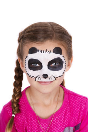 painted face: Young girl wearing panda carnival face paint isolated on white
