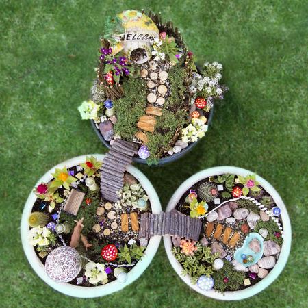 fairy garden: Birds eye view of fairy garden in a flower pot with walking path, wooden bridges and a fairy house.