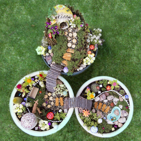 Birds eye view of fairy garden in a flower pot with walking path, wooden bridges and a fairy house.