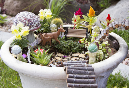 Fairy garden with deer, gazing balls and mushrooms in a flower pot