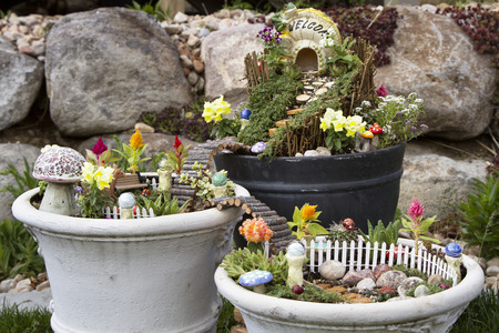 Fairy garden in a flower pot with walking path, wooden bridges and a fairy house.
