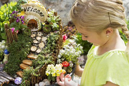 Child looking at fairy garden with a house made of a mushroom with a path and stairs in a flower pot