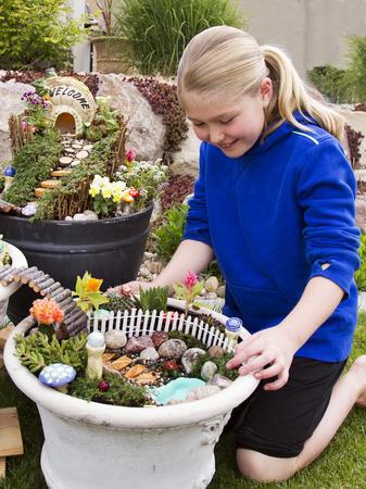 fairy garden: Young girl helping to make fairy garden in a flower pot outdoors