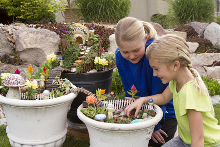 garden: Two young girls helping to make fairy garden in a flower pot outdoors Stock Photo
