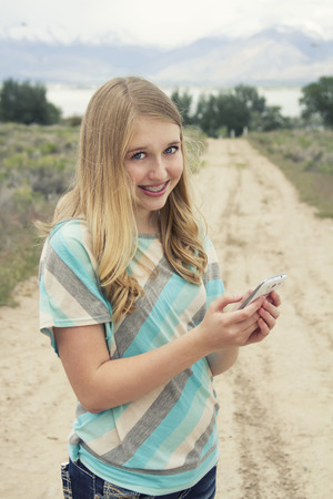 Teenage girl using cellphone walking down a country dirt road outdoors in a rural area photo