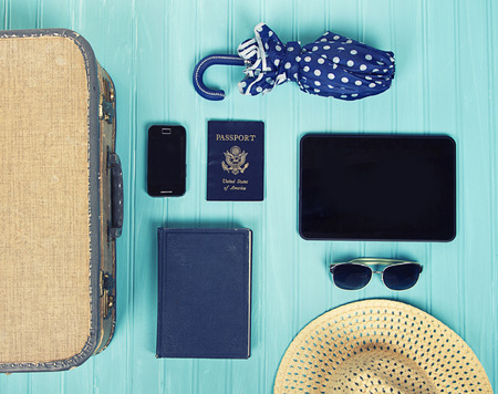 Collection of vacation travel items with a vintage filter on a turquoise backgrou