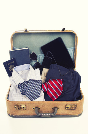 accesories: collection of business travel items in a suitcase with a vintage filter
