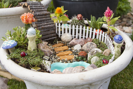 Fairy garden with a white picket fence, gazing balls and pond in a flower pot Banque d'images