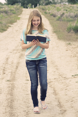 Happy teenage girl reading a book while walking down a dirt road in rural area photo
