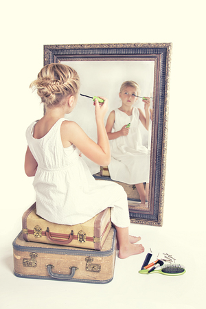full length mirror: Child or young girl putting on make-up while looking at herself in a mirror, sitting on vintage luggage, with a fish tail braid in her hair. Vintage or retro filter applied. Stock Photo