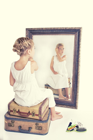 full length mirror: Child or young girl fixing her hair while looking at herself in a mirror, sitting on vintage luggage, with a fish tail braid in her hair. Vintage or retro filter applied.