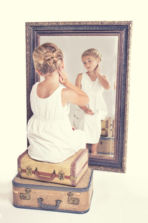 full length mirror: Child or young girl staring at herself in a mirror, sitting on vintage luggage, with a fish tail braid in her hair. Vintage or retro filter applied. Stock Photo