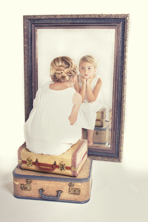 reflection: Child or young girl staring at herself in a mirror, sitting on vintage luggage, with a fish tail braid in her hair. Vintage or retro filter applied. Stock Photo