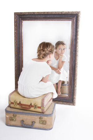 Child or young girl staring at herself in a mirror, sitting on vintage luggage, with a fish tail braid in her hair.
