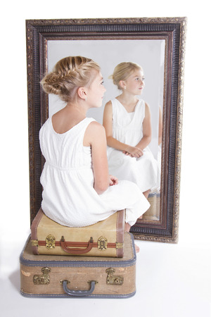 Child or young girl in front of a mirror, sitting on vintage luggage, with a fish tail braid in her hair.