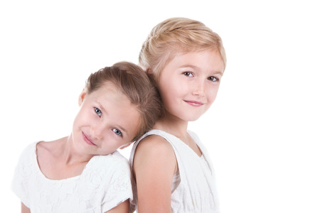 cute little girl: Two best friends sitting back to back isolated on a white background Stock Photo