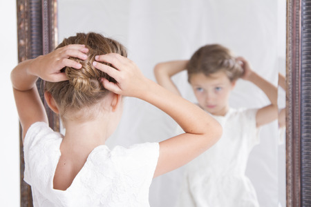 reflection mirror: Child or young girl fixing her hair while looking in the mirror. Stock Photo