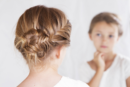 Child or young girl staring at herself in a mirror, with a fish tail braid in her hair. Stock Photo
