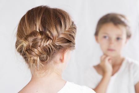 espejo: Niño o niña mirando a sí misma en un espejo, con una cola de pescado trenza en el pelo.