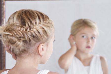 mirror face: Child or young girl fixing her hair while looking in the mirror. Stock Photo
