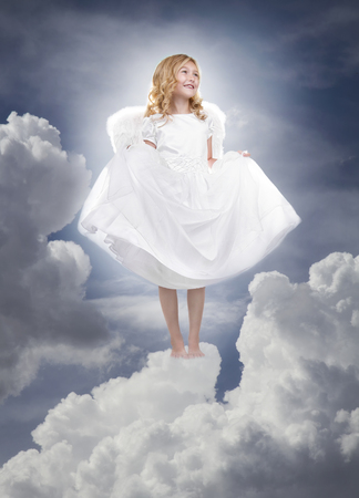 heavenly angel: Child or girl angel wearing a white dress standing on fluffy clouds in the sky