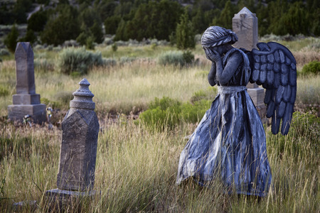 heavenly angels: Girl wearing a home made life like angel costume in an old grave yard