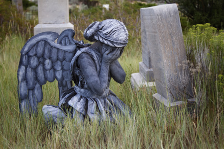 weeping angel: Girl wearing a home made life like angel costume in an old grave yard
