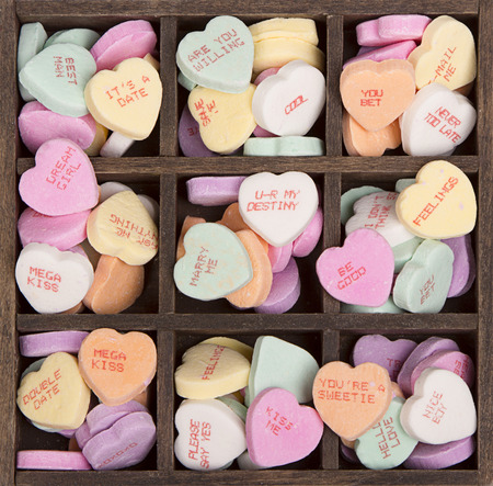 compartments: Candy conversation hearts  in a wooden box with nine compartments with hearts scattered on a white background