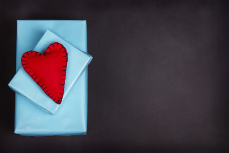 black fabric: Handmade felt hearts with black stitching sitting on presents on a blank blackboard or chalkboard.