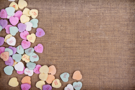 heart background: Candy conversation hearts scattered on a rustic textured brown background