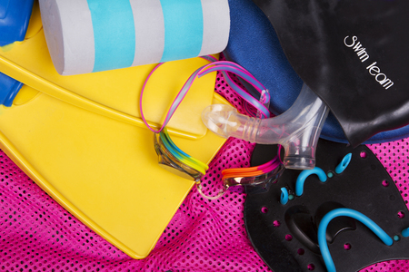 swim: Competitive swimming equipment or gear for swim team including goggles, fins, and kick board on a pink net swim bag Stock Photo