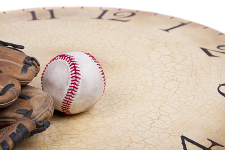 used: A baseball and mitt on an old vintage clock on an isolated white background