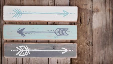 turquesa: Tres flechas pintadas a mano en un tablón de madera sobre un fondo de madera áspera
