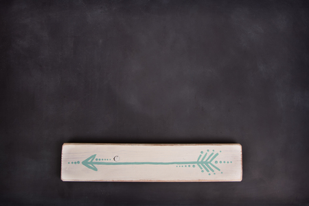 One hand painted arrow on a wooden plank on a blackboard background