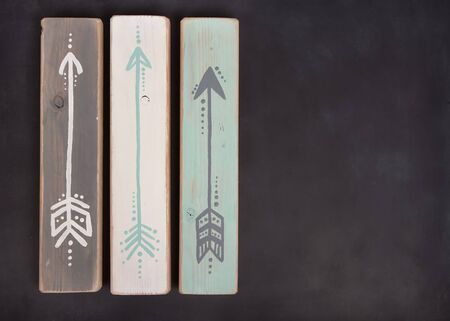 abstract grunge: Three hand painted arrows on a wooden plank on a blackboard background