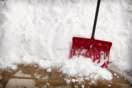 Red snow shovel in a snow bank on pavement Archivio Fotografico