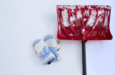 Red snow shovel with mittens lying in the snow