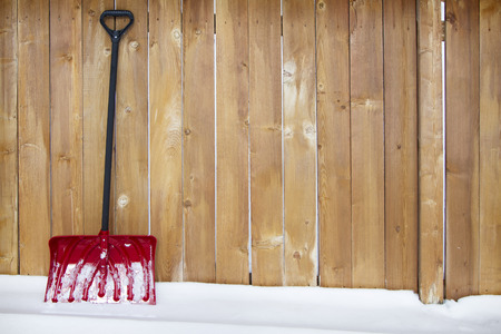 Red snow shovel leaning up against a fence on a snow drift Foto de archivo