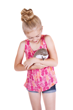 A young girl holding her pet hedgehog on an isolated white background