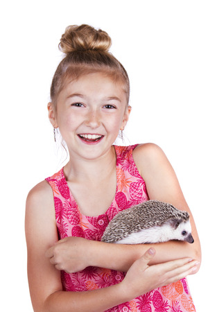 A laughing young girl having fun with her pet hedgehog on an isolated white background