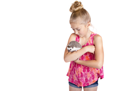 A young girl hugging her pet hedgehog, isolated on a white background Foto de archivo
