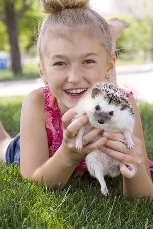 Young girl holding a pet hedgehog outside in the summer Foto de archivo