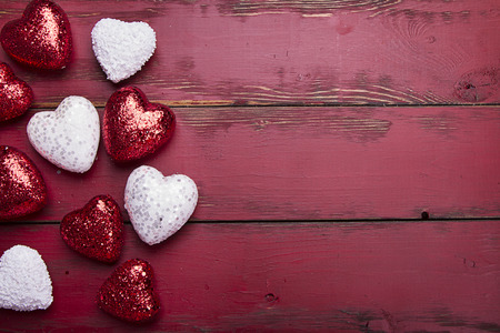 red and white glitter hearts on a red wooden background Foto de archivo