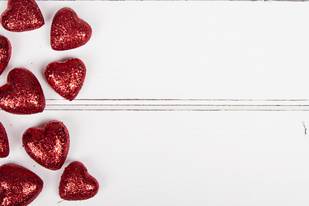 Red glitter hearts on a white wooden background Foto de archivo