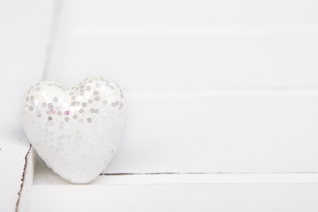 White glitter hearts on a white wooden background