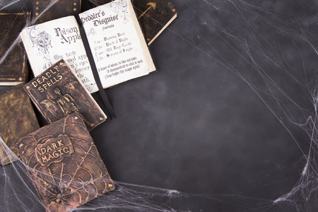 Old spell books with spider webs on a chalkboard background for Halloween.