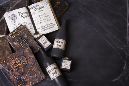Old spell books with spider webs and potion bottle on a chalkboard background for Halloween.  Foto de archivo