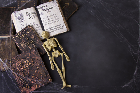 Old spell books with spider webs and skeleton on a chalkboard background for Halloween. Foto de archivo