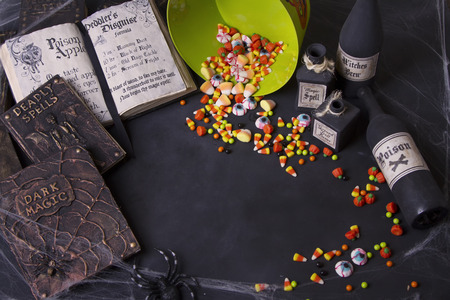 Old spell books and Halloween candy spilling out of a bucket with spider webs and potion bottle on a black chalk board background.