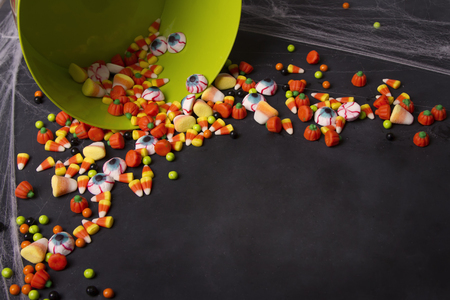 Halloween candy spilling out of a green bucket onto a black chalk board with spider webs.